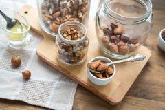 Geassorteerde noten: okkernoten, amandelen, hazelnoten en honing Stock Foto