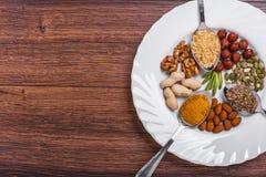 Geassorteerde noten in witte kom, plaat op houten oppervlakte Hoogste mening met exemplaarruimte Stock Foto