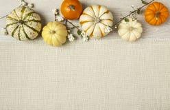 Geassorteerde oranje en witte pompoenen op geweven witte stoffenachtergrond Horizontaal beeld met exemplaarruimte Stock Afbeeldingen