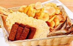 Geassorteerde snacks voor bier: de in de zon gedroogde vissen, chips, zoutten crackers, de croutons van het roggebrood in mand royalty-vrije stock afbeeldingen