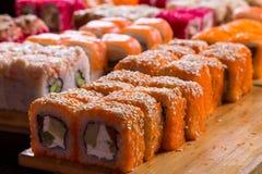 Geassorteerde sushi en broodjes op houten raad in donker licht Stock Foto's