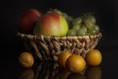 Geassorteerde vruchten Apple, pruim en druiven in een mand op een zwarte achtergrond Stock Fotografie