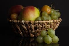 Geassorteerde vruchten Apple, pruim en druiven in een mand op een zwarte achtergrond Royalty-vrije Stock Foto's