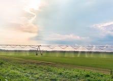 Geautomatiseerd de sproeierssysteem van de de landbouwirrigatie op gecultiveerd landbouwlandschapsgebied bij zonsondergang stock afbeeldingen