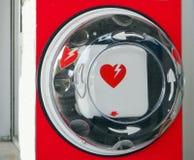 Geautomatiseerde externe defibrillator, of AED, met zijn internationaal symbool die in een openbare ruimte hangen stock foto