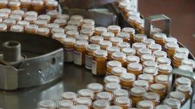 Geautomatiseerde productie van geneesmiddelen Verpakking van tabletten in een glascontainer stock videobeelden