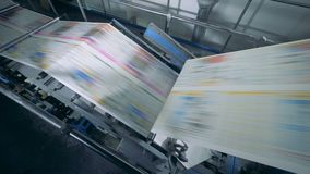 Geautomatiseerde transportband bewegende krant in een drukbureau, typografiefaciliteit stock videobeelden