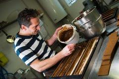 Gebäck in seiner Werkstatt, die Schokoladen-Julblöcke vorbereitet Lizenzfreies Stockbild