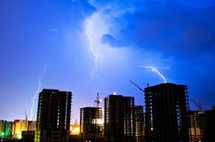 Gebäude auf einem Hintergrund des Blitzgewitter-Industriestadtbaus Lizenzfreie Stockbilder