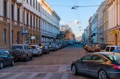 Gebäude der klassischen Architektur in der Straße mit modernen Autos und dem Himmel Lizenzfreie Stockfotografie