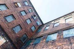 Gebäude des roten Backsteins mit Fenstern Stockfotografie
