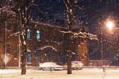 Gebäude des roten Backsteins nahe dem Park im Winter, im schlechten Wetter, im Wind und im Schneeblizzard nachts Stockfotografie