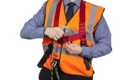 Gebäude-Feldmesser in der orange Sichtweste, die Abzugsleine zu befestigt Lizenzfreies Stockbild