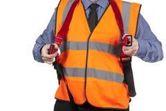 Gebäude-Feldmesser in der orange Sichtweste, die auf Sicherheitsgurt sich setzt lizenzfreie stockfotografie