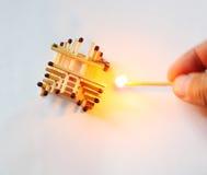 Gebäude Matchsticks und Burning einer in der Hand Lizenzfreie Stockfotografie