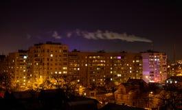 Gebäude nachts mit Fabrik rauchen über ihnen Stockfotografie