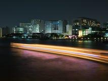 Gebäude nahe dem Fluss und eine Orange mit Blaulichtlinie der Boa Stockfotografie