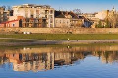 Gebäude reflektiert im Wasser von Fluss, gesetztes Licht der Wintersonne, Wisla-Fluss, Krakau, Polen Stockbilder