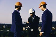Gebäude und Technikkonzept Männer mit Bart und starke Gesichter machen Anmerkungen Führergriffclipordner und -stift stockfotos