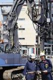 Gebäudearbeitskräfte mit schwerer Maschinerie Stockbilder