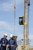 Gebäudearbeitskräfte und -kran in der Tätigkeit Stockbild