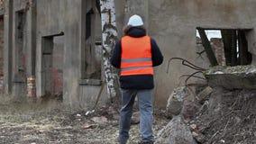 Gebäudeaufsichtskraft, die Tablet-PC auf Gebäudegebiet vor Demolierung verwendet stock footage
