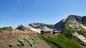 Gebäudebergwachthoch in den Bergen Schnee im Sommer auf den Steigungen der Berge stockbild