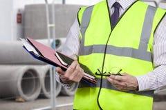 Gebäudefeldmesser in tragenden Arbeitsordnern der Warnweste stockfoto