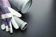 Gebäudehandschuh und -Abflussrohr auf Grau Stockbilder