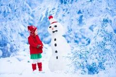 Gebäudeschneemann des kleinen Mädchens im Winter lizenzfreie stockfotografie