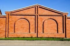 Gebäudewand des roten Ziegelsteines mit Dekorationen. Stockfoto