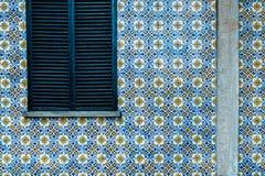 Gebäudewand verzierte alten Keramikziegel Geschlossenes Fenster mit hölzernem Jalousie stockfotografie