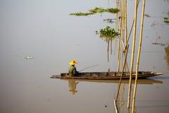 Gebürtiger asiatischer Fischer, der auf dem Boot sitzt Stockbilder