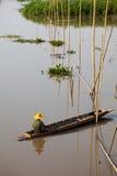Gebürtiger asiatischer Fischer, der auf dem Boot sitzt Lizenzfreies Stockfoto