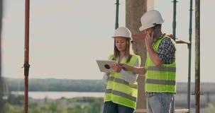 Geb?ude im Bau mit einer Frau und m?nnliche Erbauer, Erbauer, Ingenieure, die entlang ihn gehen stock video footage
