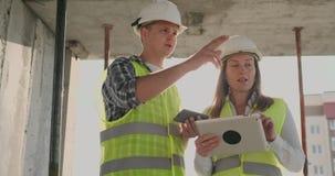 Geb?ude im Bau mit einer Frau und m?nnliche Erbauer, Erbauer, Ingenieure, die entlang ihn gehen stock footage