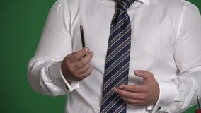 Gebaar mannelijke hand met een pen op een groene achtergrond stock videobeelden