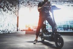 Gebaard getatoeeerd mannetje die hipster mobiele telefoon na het berijden met behulp van door elektrische autoped in de stad stock afbeeldingen