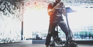Gebaard getatoeeerd mannetje die hipster mobiele telefoon na het berijden met behulp van door elektrische autoped in de stad wijd royalty-vrije stock foto