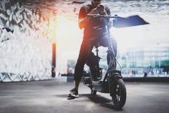 Gebaard getatoeeerd mannetje in zonnebril die smartphone na het berijden gebruiken door elektrische autoped in de stad stock fotografie