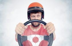 Gebaard mannetje in rode helm met stuurwiel het concept van de autobestuurder stock foto