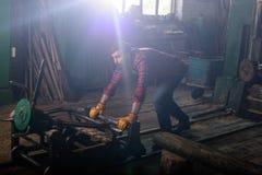 gebaarde arbeider in beschermende handschoenen die machine duwen stock fotografie