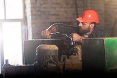 gebaarde arbeider die in beschermende helm werktuigmachine herstellen stock foto's