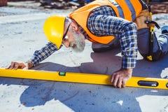 Gebaarde arbeider in weerspiegelend vest en bouwvakker die met waterpas bij bouwwerf werken, het nivelleren stock afbeeldingen