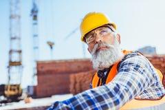 Gebaarde arbeider in weerspiegelende vest en bouwvakkerzitting bij bouwwerf royalty-vrije stock afbeeldingen