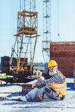 Gebaarde arbeider in weerspiegelende vest en bouwvakkerzitting bij bouwwerf en het kijken stock foto