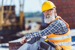 Gebaarde arbeider in weerspiegelende vest en bouwvakkerzitting bij bouwwerf en het kijken stock fotografie