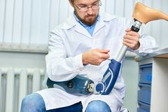 Gebaarde Arts Assembling Prosthetic Leg stock foto's