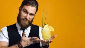 Gebaarde barman met de cocktail van de baardholding in vest stock fotografie