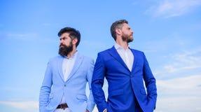 Gebaarde bedrijfsmensen die vol vertrouwen stellen Perfectioneer in elk detail De bedrijfsmensen bevinden zich blauwe hemelachter stock afbeeldingen